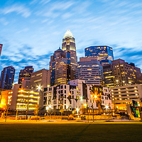 Charlotte skyline at dusk panorama photo with Romare Bearden Park, downtown Charlotte city buildings, and a beautiful blue sky. Charlotte. North Carolina is a major city in the Eastern United States of America.