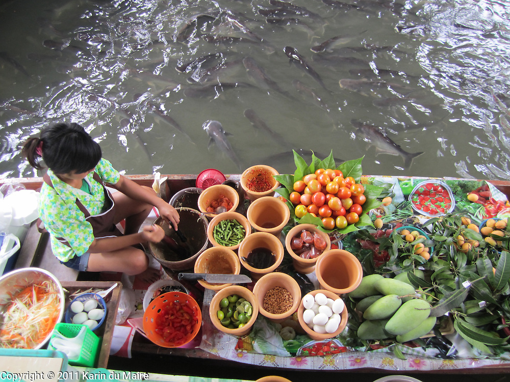 Woman preparing food on a boat at the Taling Chan Floating Market in Bangkok, Thailand. Plenty of fish!