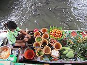 Woman preparing food on a boat at the Taling Chan Floating Market in Bangkok, Thailand. Plenty of fish!