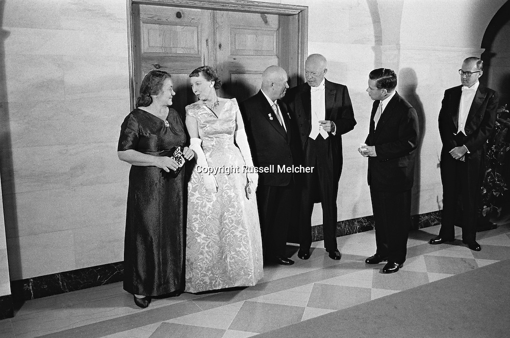 1959.  Nikita Khrushchev's wife, Nina, talking to Mamie Eisenhower, and Khruschev talking to Ike Eisenhower, President of the United States, in full gala tenue.<br />