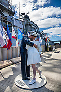 "On the dock beside USS Missouri at Pearl Harbor, ""Embracing Peace"" (by sculptor Seward Johnson) recalls the iconic Alfred Eisenstaedt photograph, ""V-J Day in Times Square,"" of a US Navy sailor kissing a stranger in New York City's Times Square on Victory over Japan Day (August 14, 1945). The photo was published in Life magazine with the caption, ""In New York's Times Square a white-clad girl clutches her purse and skirt as an uninhibited sailor plants his lips squarely on hers."" Ordered in 1940 and active in June 1944, the USS Missouri (""Mighty Mo"") was the last battleship commissioned by the United States. She is best remembered as the site of the surrender of the Empire of Japan which ended World War II on September 2, 1945 in Tokyo Bay. In the Pacific Theater of World War II, she fought in the battles of Iwo Jima and Okinawa and shelled the Japanese home islands. She fought in the Korean War from 1950 to 1953. Decommissioned in 1955 into the United States Navy reserve fleets (the ""Mothball Fleet""), she was reactivated and modernized in 1984 and provided fire support during Operation Desert Storm in January-February 1991. The ship was decommissioned in March 1992. In 1998, she was donated to the USS Missouri Memorial Association and became a museum at Pearl Harbor, on the island of Oahu, Hawaii, USA. For this photo's licensing options, please inquire."