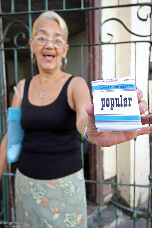 Local woman shows off a pack of Pupular brand cigarettes. Cienfuegos, Cuba. January 2009.