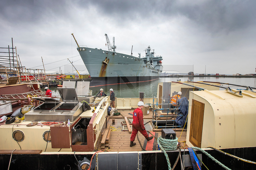 "© Licensed to London News Pictures. 04/05/2016. Birkenhead UK. Picture shows restoration work being carried out on the Daniel Adamson at Camel Laird docks in the shadow of RFA Wave Ruler. The Daniel Adamson steam boat has been bought back to operational service after a £5M restoration. The coal fired steam tug is the last surviving steam powered tug built on the Mersey and is believed to be the oldest operational Mersey built ship in the world. The ""Danny"" (originally named the Ralph Brocklebank) was built at Camel Laird ship yard in Birkenhead & launched in 1903. She worked the canal's & carried passengers across the Mersey & during WW1 had a stint working for the Royal Navy in Liverpool. The ""Danny"" was refitted in the 30's in an art deco style. Withdrawn from service in 1984 by 2014 she was due for scrapping until Mersey tug skipper Dan Cross bought her for £1 and the campaign to save her was underway. Photo credit: Andrew McCaren/LNP ** More information available here http://tinyurl.com/jsucxaq **"