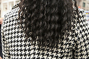 black curly hair of female person against a black and white coat