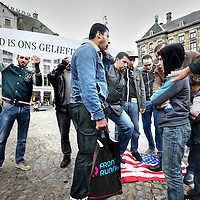 Nederland, Amsterdam , 14 september 2012..Demonstratie van Moslims op de Dam tegen de Amerikaanse anti moslim film die onlangs veel onrust heeft veroorzaakt in het midden Oosten..Op de vlag staat: Niemand is ons geliefder dan de profeet Mohammed. Symbolisch vegen de demonstranten hun voeten af aan de amerikaanse vlag..Foto:Jean-Pierre Jans