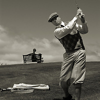 A middle aged man playing golf.