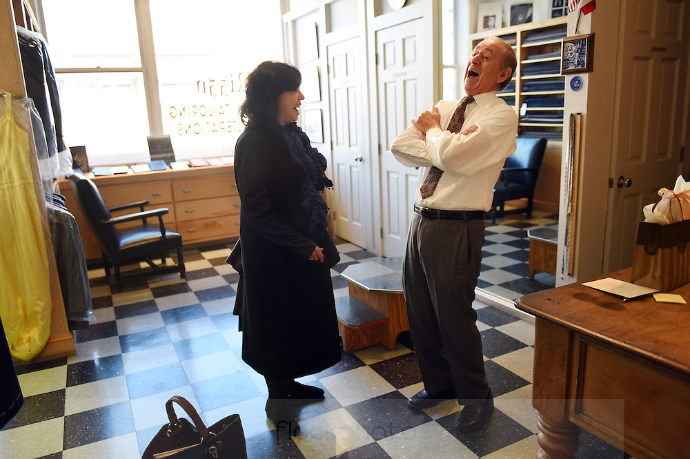 Jane Rabe, of Cambridge, has a laugh with Joe Calautti, owner of Rizzo Tailor in Harvard Square, on his last day before retiring after 50 years in business, Nov. 18, 2015. Rabe has been a customer since 1969.<br /> (Kate Flock/Cambridge Chronicle)
