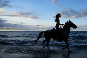 Woman riding a horse on a beach at a resort in Puerto Rico