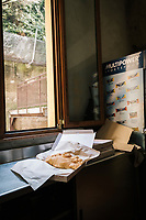 NAPLES, ITALY - 1 AUGUST 2018: A fried pizza is seen here in the makeshift temporary kitchen of Cantina del Gallo, a family-owned restaurant in the Rione Sanità in Naples, Italy, on August 1st 2018.<br /> <br /> Cantina del Gallo, in the Rione Sanità, was established in 1898 and run by four generations of the Silvestri family. The cantina began as a store selling bulk wine and oil. It was only in the 1950s, when the legendary Aunt Cuncetta began cooking, that it became the simple and genuine tavern it is today.<br /> There are three dishes that are the restaurant's workhorses, and the ones we always seem to rotate between: the pennette alla sorrentina (a variation of the classic gnocchi alla sorrentina, seasoned with tomato, basil and stringy mozzarella), the baked cod (although the fried cod is just as mouth-watering) and the pizza cafona (peasant pizza), topped with oregano, cheese, chile and with double the tomatoes (tomato juice and chopped tomatoes).