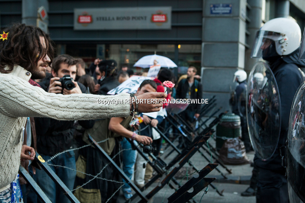 Indignados protests against the financial crisis and the power of banks and kapitalism.European Headquarters at Schumann Square is being protected by Military police and barb-wire. young protestor handing over a flower to the police. Brussels Belgium 15 october 2011