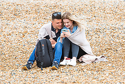 © Licensed to London News Pictures. 26/05/2019. Brighton, UK. A couple cuddle up under a blanket on the beach in Brighton and hove as cooler weather is hitting the seaside resort on the May Bank Holiday Sunday. Photo credit: Hugo Michiels/LNP