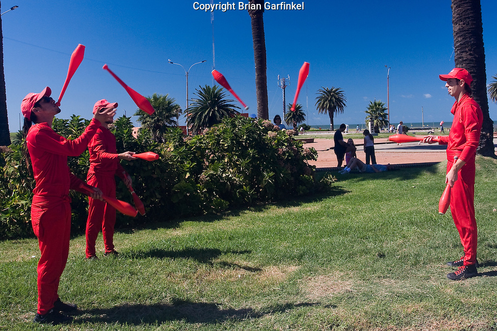 """Montevideo, Uruguay - Jugelers perform next to the beach of the river of Plata in Montevideo. These Jugelers wore red suites for the mobile phone company """"Claro"""" and are part of a curret marketing campaign"""