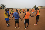 End of training prayers. Football practice and training for the under 12's team of Corners Babies youth football Academy. Two of the academy's past players now play for the national team, the Black Stars.  Kumasi- Ghana's second largest city. West Africa..©Picture Zute Lightfoot.  07939 108077. www.lightfootphoto.co.uk