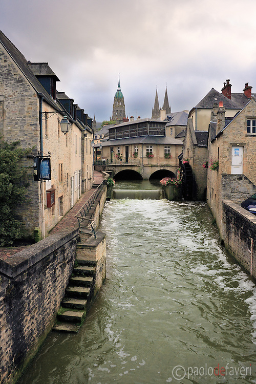 A view of downtown Bayeux, with its canals, stone buidings and cobblestone lanes, and the cathedral's bell tower and spires. .Bayeux is a wonderful medieval town located in the heart of lower Normandy, and it's the home of the Bayeux Tapestry, one of the oldest surviving complete tapestries in the world, made to commemorate events in the Norman Conquest of England in1066. The tapestry is displayed in a museum in the town centre. Bayeux is also famous for being the first French town to be liberated during the Battle of Normandy. I took this picture from atop a small bridge spanning the canal, on a cloudy evening of mid August.