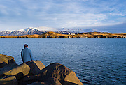 A man fishing with Viðey in the back