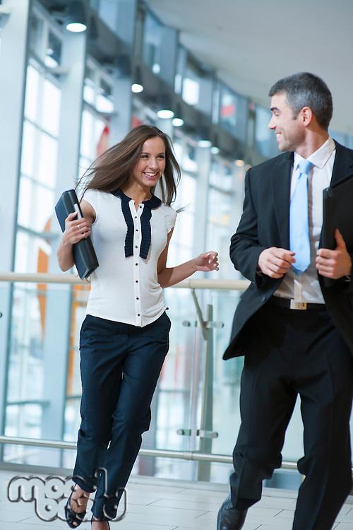 Happy businessman and businesswoman running