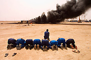 "Firefighters from the Kuwait Oil Company (called KWWK: Kuwait Wild Well Killers) pray at noon by the first oil well fire they were working on in Iraq's Rumaila Oil Field. Later in the day they extinguished this smoky fire and the next day stopped the flow of gas and oil with drilling mud using what is called a ""stinger"", a tapered pipe on the end of a long steel boom controlled by a bulldozer. Drilling mud, under high pressure, is pumped through the stinger into the well, stopping the flow of oil and gas. The Rumaila field is one of Iraq's biggest with 5 billion barrels in reserve. The burning wells in the Rumaila Field were ignited by retreating Iraqi troops when the US and UK invasion began in March 2003. Rumaila is also spelled Rumeilah."