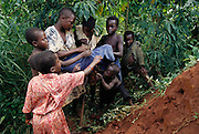 Children in the village of Bweyogerere hunt for termites early in the morning by hacking into the termites' mounded earthen homes. They place a cloth in front of the entrance, and yank off the ants that attack the cloth. They pick them up by the rear, biting off their heads and throwing away the rear part. Or they collect them in a bowl to be roasted. Bweyogerere, Uganda. Image from the book project Man Eating Bugs: The Art and Science of Eating Insects.