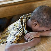 Madagascar. Boy sleeping in class.<br /> Marolondo public primary school