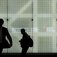 China, Hong Kong, Silhouette of shoppers walking past brightly glowing Dior store in Kowloon Peninsula on winter evening
