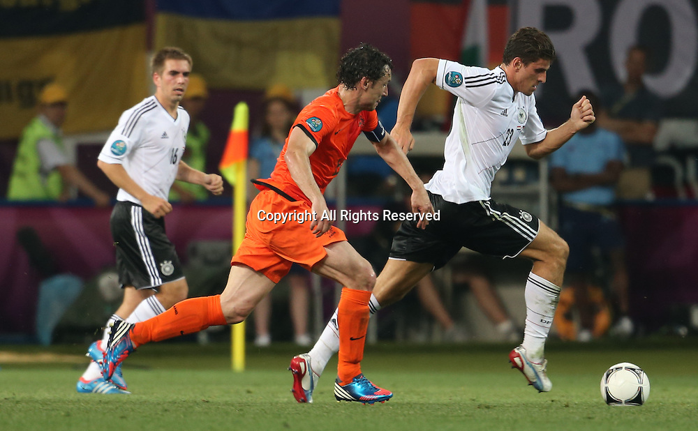 13.06.2012 Ukraine, Kharkiv.  Netherlands national team player Mark van Bommel (center) and German national team players Mario Gomez (R), Philipp Lahm (L)  in the group stage European Football Championship match between teams of the Netherlands and Germany.