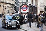 A British passenger gets into a Black Taxi cab outside Bank Underground Station in central London, United Kingdom.  The famous traditional Black Cabs are an iconic image of London and can either be booked in advance or hailed on the streets or from designated taxi ranks.  The taxis official name is Hackney Carriage.