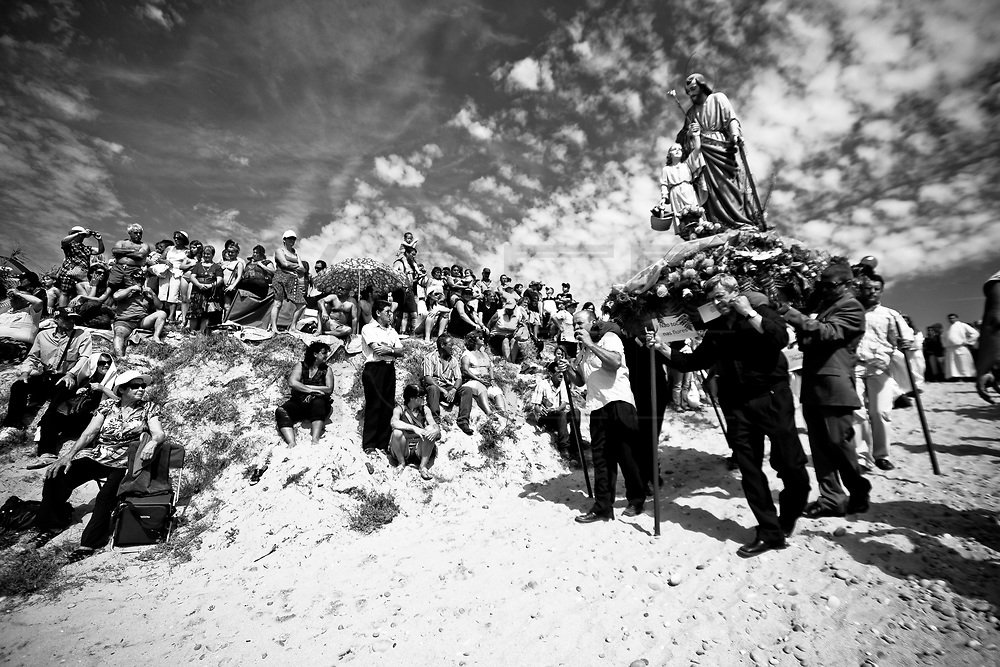Men carrie a litter with the image of Saint Peter during  St. Bartolomeu celebrations while people assist on the dunes of the beach. The procession to thank the Saint incorporates hundreds of extras and large litters, which reconstruct biblical episodes. This tradition that dates back to the sixteenth century (1566), and it claims the devil is on the loose during this day. Every year on 24 August  faith and tradition join thousands of people at the feast of St. Bartolomeu do Mar, for ritual that mixes the sacred and the profane.