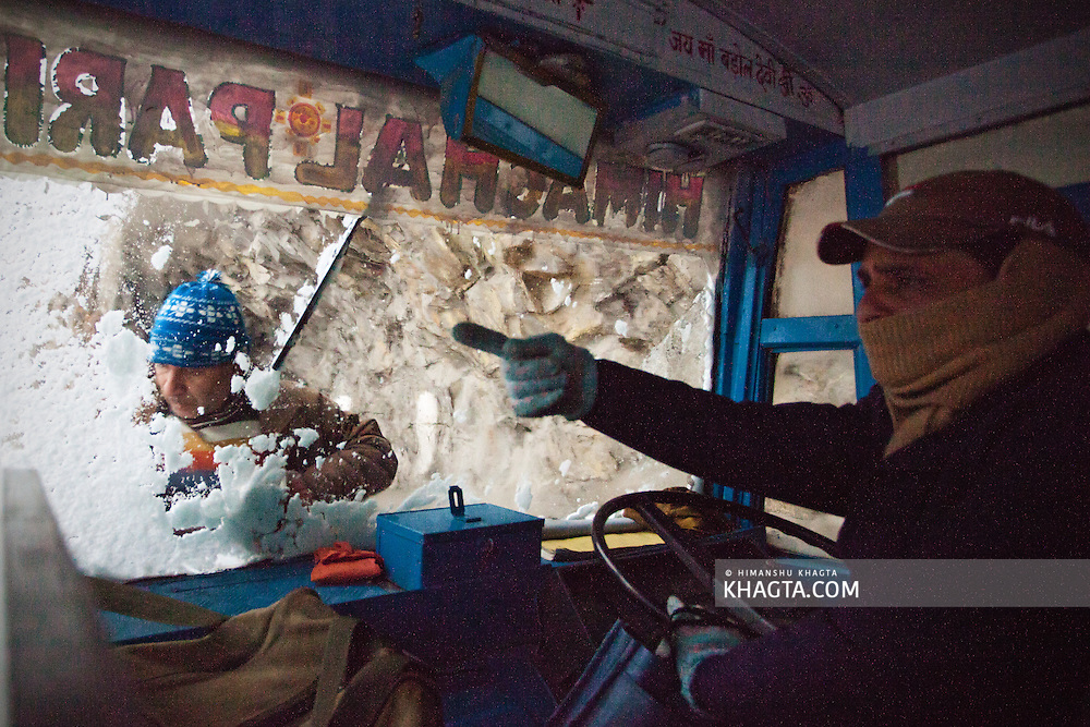 Driver instructs the conductor to clean the screen that got covered in snow while driving down from Sangla through a snow storm. <br />