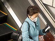 Asian woman with protective mask standing on an escalator