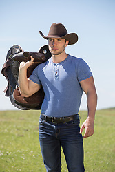 hot All American cowboy with a saddle on a ranch