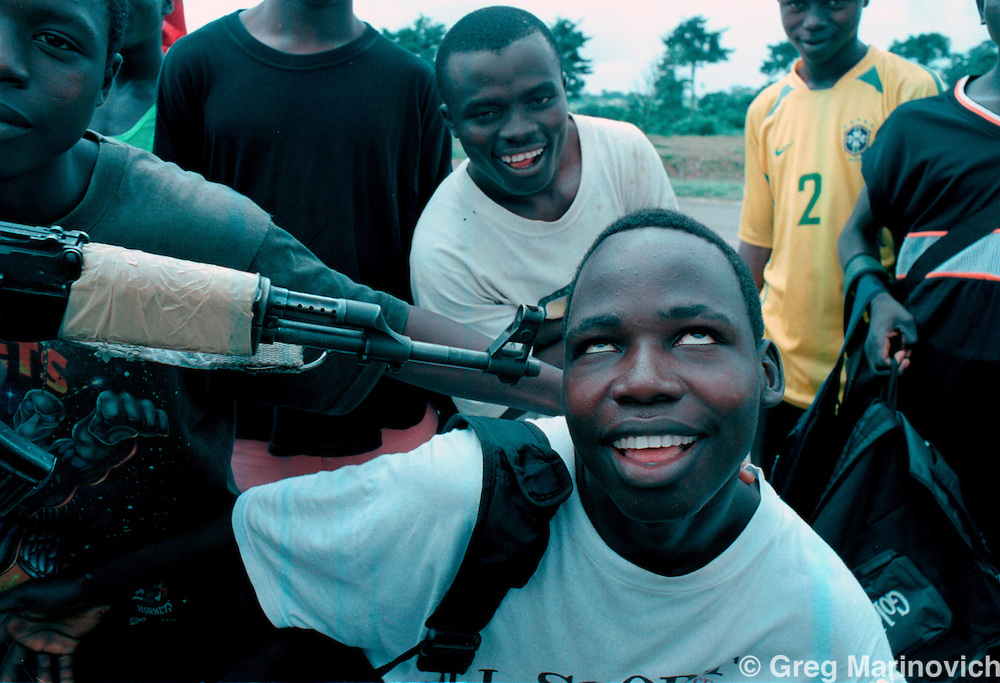 IPMG0887 Bo Waterfront, Liberia. A group of LURD rebels and child soldiers loyal to Sekouh Conneh Jr fool around at the border crossing with Sierra Leone at Bo Waterfront, Sept 22, 2003. Liberia's decades long civil conflict has destabilised the entire region and turned a generation of youth into fighters.  Greg Marinovich/South Photographs