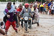 Dar es Salaam, Tanzania -   2015-05-07  - With some helping hands,  a motorcyclist and his passenger make their way across flooded Morogoro Road in Dar es Salaam, Tanzania on May 7, 2015. The Tanzania Meteorological Agency warned of 50mm of rainfall on May 6 and 7 due to a low pressure system developing in the Indian Ocean.  Photo by Daniel Hayduk
