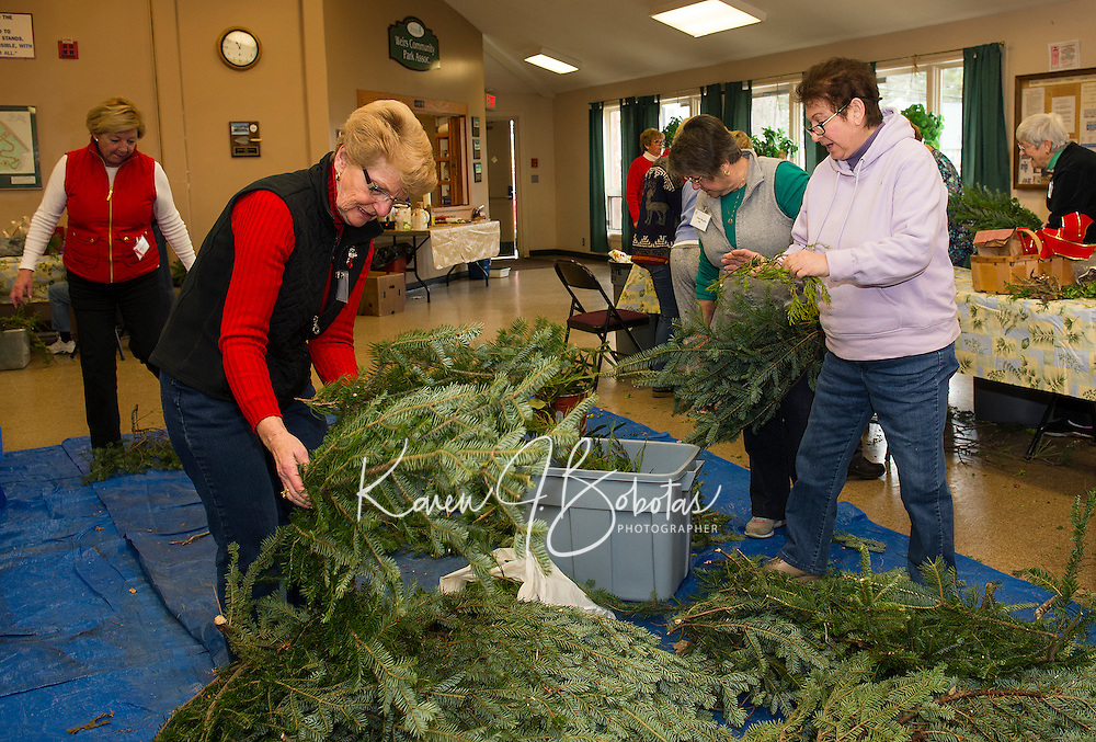 Members of the Opechee Garden Club dive into a mound of greens as they put together approximately 90 floral arrangements to be delivered to the Belknap County Nursing Home residents on Tuesday.  (Karen Bobotas/for the Laconia Daily Sun)