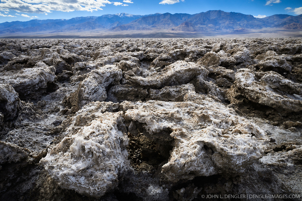 The Devil&rsquo;s Golf Course is a large saltpan in Death Valley National Park. The salt is the result of mineral rich water evaporating until only the salts remain. Wind and rain shape the salt crystals into jagged, and often sharp, formations. Exploratory holes drilled prior to Death Valley becoming a national monument show that the salt and gravel beds of the Devil&rsquo;s Golf Course are 1,000 feet deep or more. In the background is the Panamint Range.<br /> <br /> Death Valley National Park, located in eastern California near the border with Nevada is one of the hottest spots on earth, holding the hottest recorded air temperature of 134 &deg;F. The Park also is location of the lowest spot in North America, 282 feet below sea level at the vast salt flats at Badwater Basin. At 3.4 million acres, the park is the largest national park in the contiguous United States. Death Valley National Park sits between the Panamint Range on the west  and Amargosa Range on the east.