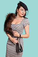 Beautiful young woman in dress carrying fur boa on her shoulder against blue background
