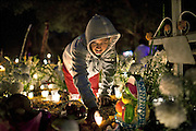 Girl lights a candle for her loved one during the Day of the Dead celebration in Tzintzuntzan, Mexico.