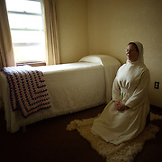 "Sister Michele Armstrong prays in her ""cell"" at Our Lady of the Mississippi Abbey, a monastery of Trappist nuns.  Armstrong, a novice at the convent, spends time each day in private prayer and communion with God.  The community of 22 Roman Catholic women follow Jesus Christ through a life of prayer, silence, simplicity and ordinary work.  Their home is a beautiful monastery which sits high on a bluff, overlooking the Mississippi River."