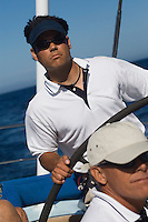 Man at Helm of Sailboat on ocean