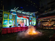 "30 JUNE 2016 - BANGKOK, THAILAND:  Fireworks are set off, signifying the start of a Chinese opera performance at Chiao Eng Piao Shrine in Bangkok. Chinese opera was once very popular in Thailand, where it is called ""Ngiew."" It is usually performed in the Teochew language. Millions of Chinese emigrated to Thailand (then Siam) in the 18th and 19th centuries and brought their culture with them. Recently the popularity of ngiew has faded as people turn to performances of opera on DVD or movies. There are about 30 Chinese opera troupes left in Bangkok and its environs. They are especially busy during Chinese New Year and Chinese holidays when they travel from Chinese temple to Chinese temple performing on stages they put up in streets near the temple, sometimes sleeping on hammocks they sling under their stage.      PHOTO BY JACK KURTZ"