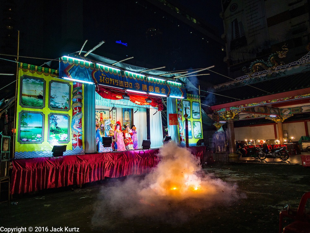"""30 JUNE 2016 - BANGKOK, THAILAND:  Fireworks are set off, signifying the start of a Chinese opera performance at Chiao Eng Piao Shrine in Bangkok. Chinese opera was once very popular in Thailand, where it is called """"Ngiew."""" It is usually performed in the Teochew language. Millions of Chinese emigrated to Thailand (then Siam) in the 18th and 19th centuries and brought their culture with them. Recently the popularity of ngiew has faded as people turn to performances of opera on DVD or movies. There are about 30 Chinese opera troupes left in Bangkok and its environs. They are especially busy during Chinese New Year and Chinese holidays when they travel from Chinese temple to Chinese temple performing on stages they put up in streets near the temple, sometimes sleeping on hammocks they sling under their stage.      PHOTO BY JACK KURTZ"""