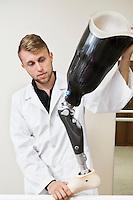 Young technician working on prosthetic leg