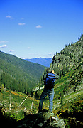Hiker taking photographs in the Scotchman Peaks Roadless Area. Kootenai National Forest in the Cabinet Mountains, northwest Montana
