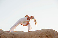 Senior woman in yoga pose on the rocks.