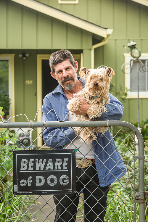 """He's a lot meaner than he looks.""  Professional gardener and 40 year resident of Calistoga, Lorenzo Perez stands at his front gate with his guard dog, Gramon."