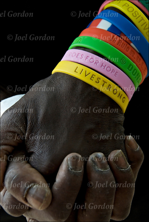 Hands of African American male wearing eight different colorful plastic wrist bracelets. Each color is for a different cause. The yellow is for the Lance Armstrong Cancer Prevention and Survival. <br /> <br /> Now these bracelets can be seen as fads.