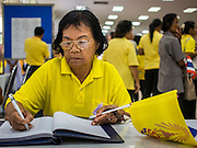 28 NOVEMBER 2014 - BANGKOK, THAILAND:  A woman with the Monarchal flag at Siriraj Hospital signs a book of birthday greetings for Bhumibol Adulyadej, the King of Thailand. The King was born on December 5, 1927, in Cambridge, Massachusetts. The family was in the United States because his father, Prince Mahidol, was studying Public Health at Harvard University. He has reigned since 1946 and is the world's currently reigning longest serving monarch and the longest serving monarch in Thai history. Bhumibol, who is in poor health, is revered by the Thai people. His birthday is a national holiday and is also celebrated as Father's Day. He is currently hospitalized in Siriraj Hospital, recovering from a series of health setbacks. Thousands of people come to the hospital every day to sign get well cards for the King. People wear yellow at events associated with the King because he was born on a Monday, and yellow is Monday's color in Thai culture. It's also the color of the monarchy.      PHOTO BY JACK KURTZ