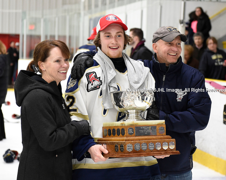TORONTO, ON - Apr 22, 2015 : Ontario Junior Hockey League game action between the Toronto Patriots and the Kingston Voyaguers. Game seven of the Buckland Cup Championship Series. Jacob Hayhurst #12 celebrates with his parents and the Buckland Cup.<br /> (Photo by Andy Corneau / OJHL Images)
