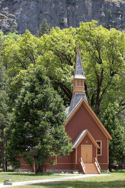 Summer view of Yosemite Chapel under green trees in Yosemite National Park, California