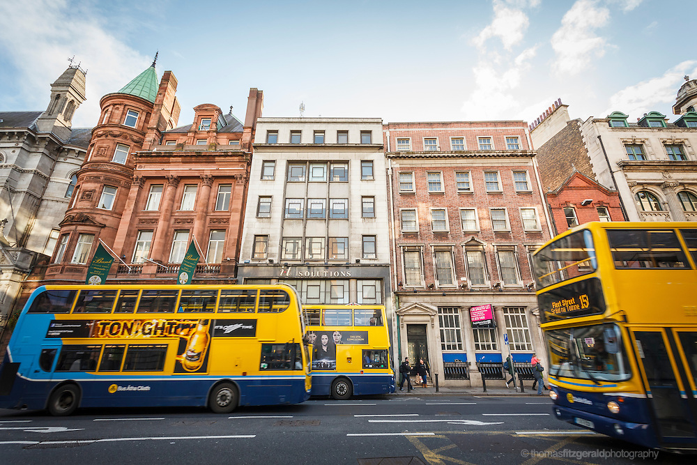 2012: Dublin, Ireland. Busses pass by on a busy Dame Street in Dublin