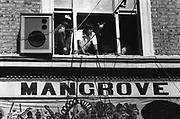 People looking out of an upstairs window, next to a speaker, Notting Hill, London, UK, 1983.